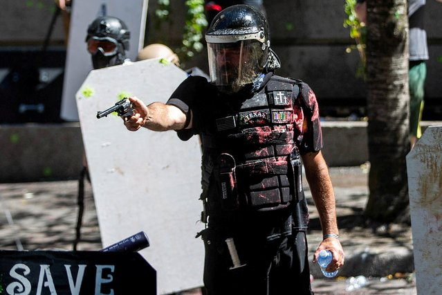 Alan Swinney points a gun during clashes between groups like Proud Boys and Patriot Prayer, and protesters against police brutality and racial injustice in Portland, Oregon, U.S., August 22, 2020. (Photo by Maranie Staab/Reuters)