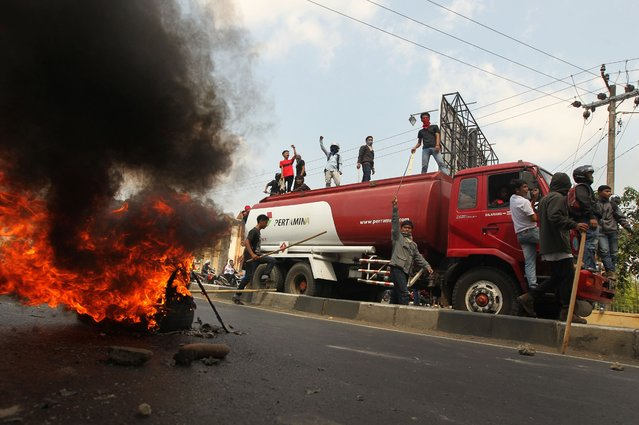 Students commandeer a fuel truck during protests outside a university in Makassar, located in South Sulawesi province on November 6, 2014 to denounce the planned increase of fuel prices as the Indonesian government moves to reduce the fuel subsidy blamed for a widening current account deficit. (Photo by Yusuf Wahil/AFP Photo)
