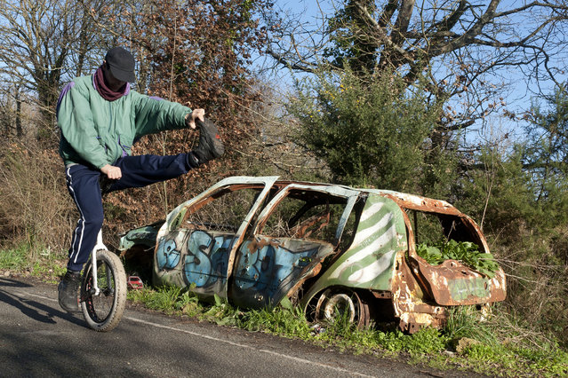 """An activist on a unicycle rides past an abandoned car that could be used as a barricade in the """"ZAD"""" (zone to defend), in Notre-Dame-des-Landes, outside the city of Nantes, western France, Wednesday, January 17, 2018. French Prime Minister Edouard Philippe says that the government has decided against building an airport in western France that has mobilized nearly a decade of sometimes violent protests and he told protesters occupying the site that they must leave. (Photo by Mathieu Pattier/AP Photo)"""