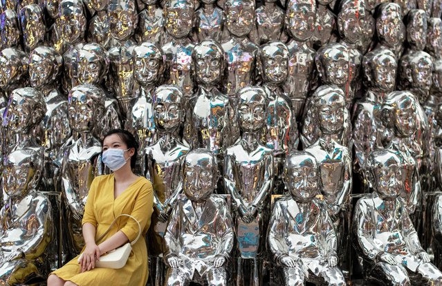 A woman wearing a face mask poses for a picture at a shopping centre in Beijing on August 23, 2020. (Photo by Noel Celis/AFP Photo)