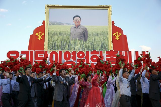 People cheer toward the stands with North Korean leader Kim Jong Un as they carry a large picture of his father and former leader Kim Jong-il during the parade celebrating the 70th anniversary of the founding of the ruling Workers' Party of Korea, in Pyongyang October 10, 2015. (Photo by Damir Sagolj/Reuters)