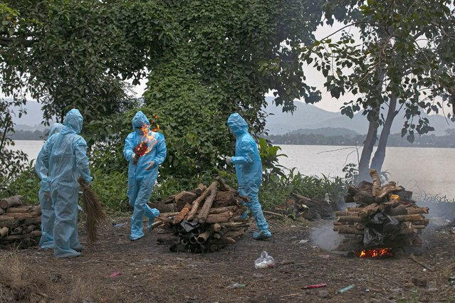 People wearing personnel protective equipment perform rituals for the cremation of a relative who died of COVID-19 in Gauhati, India, Thursday, September 10, 2020. India reported another record spike of 95,735 new coronavirus infections in the past 24 hours as the virus spreads beyond its major cities. The ministry said the surge in new infections is due to ramping of daily testing that exceeds 1 million now. However, experts caution that India's outbreak is entering a more dangerous phase as the virus spreads to smaller towns and villages. (Photo by Anupam Nath/AP Photo)