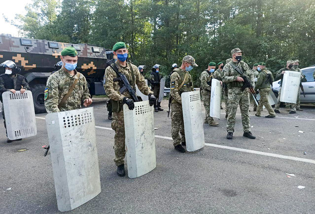 Ukrainian border guards block the road on the Belarus-Ukraine border, in Belarus, Tuesday, September 15, 2020. About 700 Jewish pilgrims are stuck on Belarus' border due to coroavirus restrictions that bar them from entering Ukraine. Thousands of pilgrims visit the city each September for Rosh Hashana, the Jewish new year. However, Ukraine closed its borders in late August amid a surge in COVID-19 infections. (Photo by TUT.by via AP Photo)