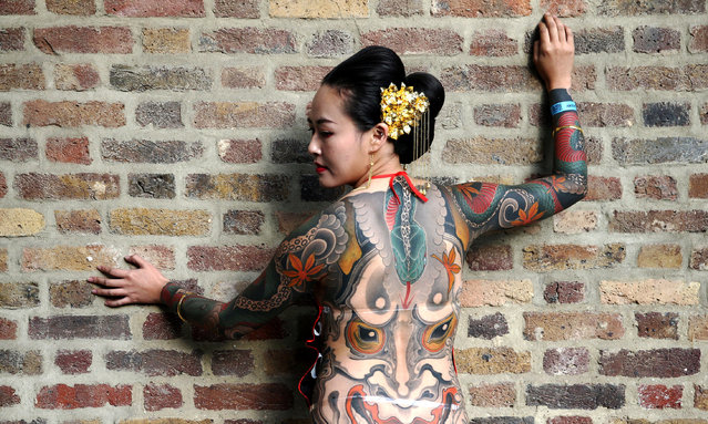 A woman with a Japanese style full back body tattoo at the 12th London International Tattoo Convention, which opened today in Tobacco Dock, east London on September 23, 2016. The show features over 400 of the world's finest, most prestigious and elite tattoo artists as well as a showcasing alternative culture in the form of piercing, burlesque and the Miss Pin Up UK competition. Around 20,000 people will attend over the weekend. (Photo by Michael Preston/Alamy Live News)