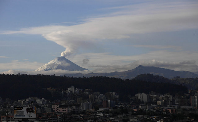 The Cotopaxi volcano spews ash and vapor, seen from Quito, Ecuador, Monday, October 19, 2015. Cotopaxi began showing renewed activity in April and its last major eruption was in 1877. (Photo by Dolores Ochoa/AP Photo)