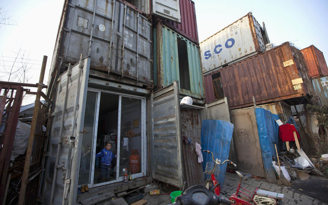 A child stands at the door of a shipping container that serves as his home March 4, 2013 in Shanghai, China. The containers, which house several families, were set up by the landlord, who charges 500 yuans (about 80 dollars) per month for each container. (Photo by Aly Song/Reuters)