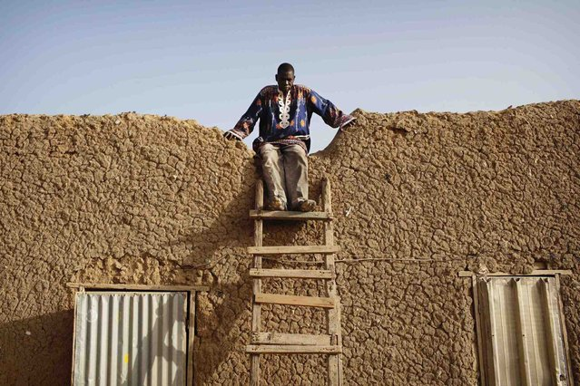 Local resident Fada Yarga prepares to climb down a ladder at his residence, a traditional mud brick house, in Gao March 11 2013. (Photo by Joe Penney/Reuters)