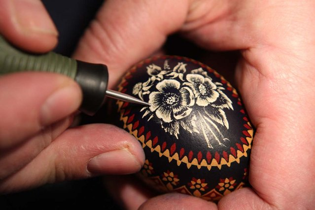 A Sorb egg painter engraves an Easter egg at the annual Easter egg market on March 16, 2013 in Schleife, Germany. Easter is a particularly important time of year for Sorbs, a Slavic minority in eastern Germany, and the period includes the tradition of painting Easter eggs that include visual elements intended to ward off evil. Many Sorbs still speak Sorbian, a language closely related to Polish and Czech.  (Photo by Adam Berry)