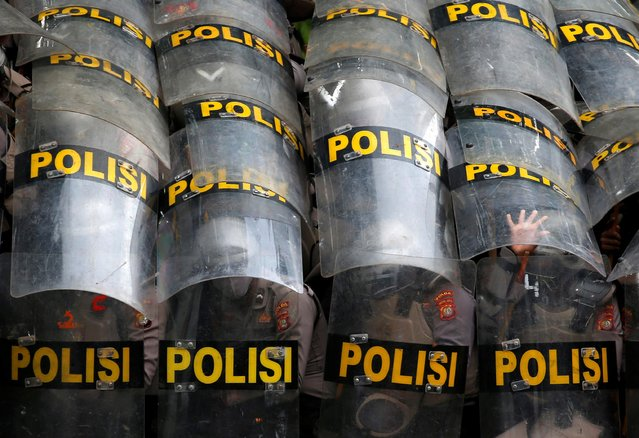 Police officers protect themselves with their shields during a protest against the new so-called omnibus law, in Jakarta, Indonesia, October 13, 2020. (Photo by Willy Kurniawan/Reuters)