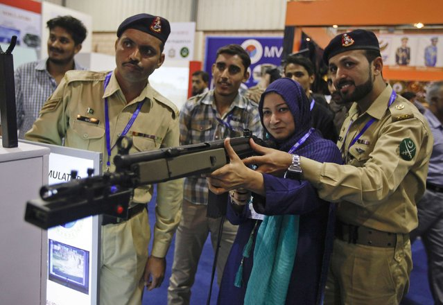 An army officer instructs a visitor as she aims a simulation gun at a target, at an exhibit during the International Defence Exhibition and Seminar (IDEAS 2014) in Karachi, December 3, 2014. (Photo by Akhtar Soomro/Reuters)