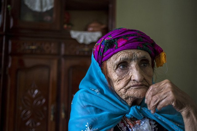 Djena Benzahra, 74, a berber woman from the Chaouia region, who has facial tattoos, sits inside her house in Ouled Azzouz in the Aures Mountain, Algeria October 9, 2015. Benzahra was forced to have a tattoo when she was 9 years old by her mother, who wanted her to look beautiful. All the girls her age were tattooed, her mother said. (Photo by Zohra Bensemra/Reuters)