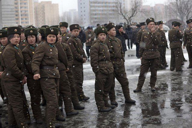 North Korean soldiers gather along a Pyongyang street during heavy snowfall on Sunday, February 17, 2013. (Photo by David Guttenfelder/AP Photo)