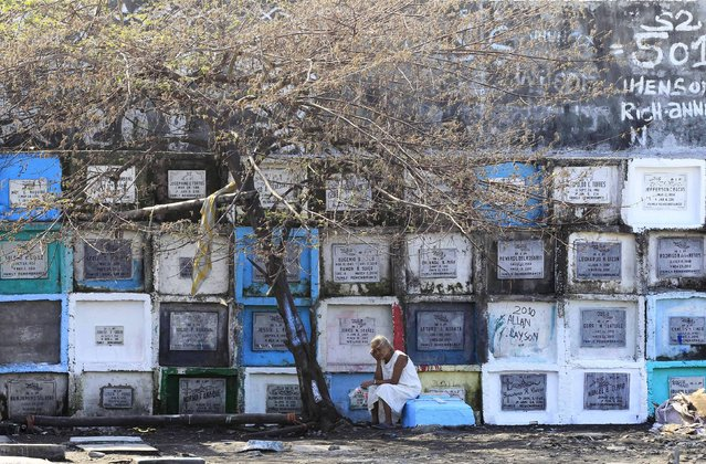 """A woman sits next to an """"apartment-style"""" grave inside a cemetery in Navotas city, north of Manila October 31, 2015. (Photo by Romeo Ranoco/Reuters)"""