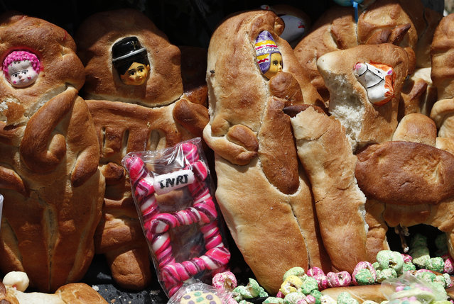 """Traditional """"Tantawawas"""" bread shaped like children sit on a grave as a Day of the Dead offering at the Villa Ingenio cemetery in El Alto, Bolivia, Monday, November 2, 2020. (Photo by Juan Karita/AP Photo)"""