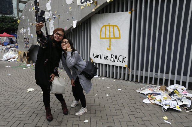 """Pro-democracy supporters take a """"selfie"""" photograph by a banner which reads """"We'll be back"""", outside the government headquarters building at the financial Central district in Hong Kong December 11, 2014. Over 10,000 protesters massed at a major pro-democracy protest site on Wednesday evening, even as authorities warned people to stay away, before the final clearance of the main """"occupy"""" camp the following morning. (Photo by Bobby Yip/Reuters)"""
