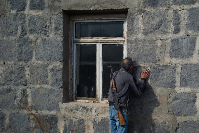 A man kisses the walls of his home before abandoning it as fear of Azeri persecution prompts him to leave his homeland on November 12, 2020 in Karvachar, Nagorno-Karabakh. Ethnic Armenians living in the Karvachar district of the disputed territory Nagorno-Karabakh said goodbye to their homes after the land had been ceded by Armenia to Azerbaijan as per a peace agreement made between the two countries on November 9, 2020. (Photo by Alex McBride/Getty Images)