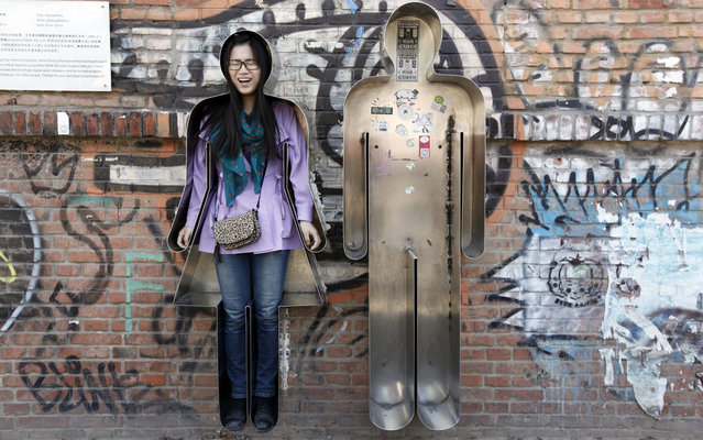 """A visitor reacts as she poses for a photograph in an art installation entitled """"You and Me"""" in Beijing's 798 art area April 18, 2013. (Photo by Jason Lee/Reuters)"""