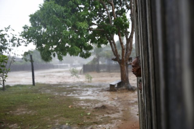 Raimundo Pereira, 64, looks at heavy rain from the window of his house in the village of Rio Pardo next to Bom Futuro National Forest, in the district of Porto Velho, Rondonia State, Brazil, August 31, 2015. (Photo by Nacho Doce/Reuters)