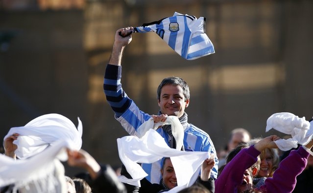 A faithful holds up an Argentina soccer shirt as Pope Francis, who's 78th birthday is today, arrives to lead his general audience at the Vatican, December 17, 2014. (Photo by Tony Gentile/Reuters)