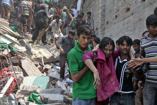 Rescuers assist an injured woman after an eight-story building housing several garment factories collapsed in Savar, near Dhaka, Bangladesh, Wednesday, April 24, 2013. Dozens were killed and many more are feared trapped in the rubble. (Photo by A. M. Ahad/AP Photo)