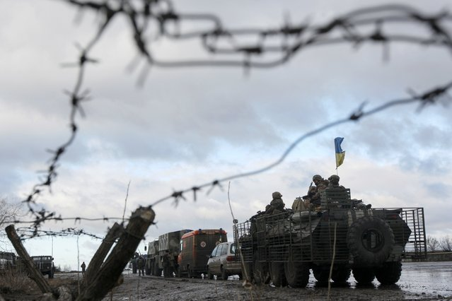 A Ukrainian military convoy is pictured through a barbed wire fence at a military base in the town of Kramatorsk, eastern Ukraine, December 24, 2014. (Photo by Valentyn Ogirenko/Reuters)
