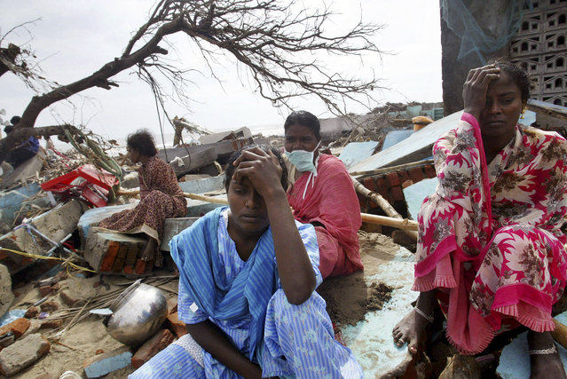 In this January 1, 2005 file photo, Lakshmi, center, Selvi, right, and Ariamala, rear with mask, grieve as earthmovers clear debris of their damaged house at a fishermen's colony which was hit by a tsunami, in Nagappattinam, in the southern Indian state of Tamil Nadu. (Photo by Gurinder Osan/AP Photo)