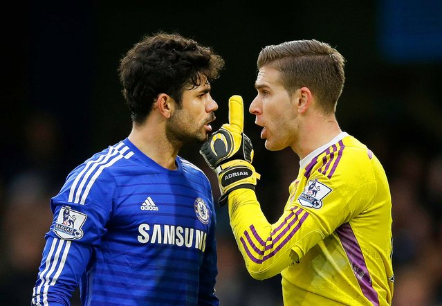 Chelsea's Diego Costa, left, argues with West Ham United's goalkeeper Adrian during the English Premier League soccer match between Chelsea and West Ham at Stamford Bridge stadium in London, Friday, December 26, 2014. (Photo by Matt Dunham/AP Photo)