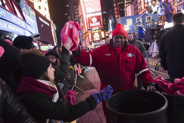 Hats are passed out to revelers in Times Square during New Year's Eve celebrations in New York December 31, 2014. (Photo by Keith Bedford/Reuters)