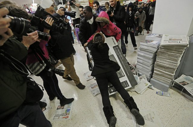 """Shoppers wrestle over a television as they compete to purchase retail items on """"Black Friday"""" at an Asda superstore in Wembley, north London, in this file photograph dated November 28, 2014. Spending in Britain on next week's """"Black Friday"""" discount shopping day looks set to break last year's record despite warnings that retailers would be wise to shun an event imported from the United States. (Photo by Luke MacGregor/Reuters)"""