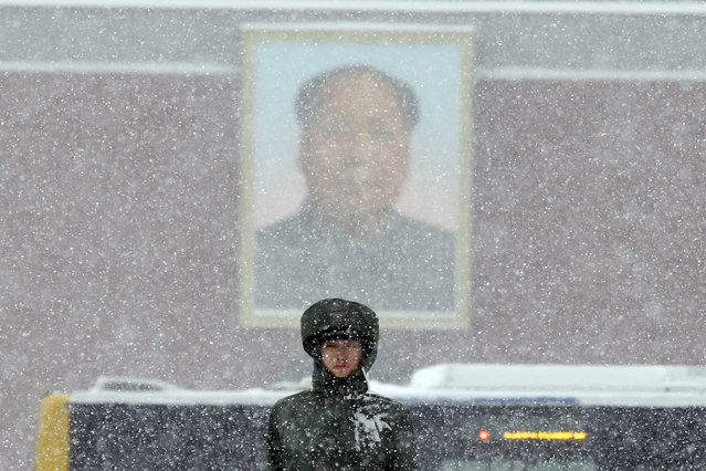 A Chinese paramilitary policeman stands on duty as heavy snow falls near a portrait of late Chinese leader Mao Zedong on Tiananmen Gate in Beijing, China, Sunday, November 22, 2015. China's meteorological authority forecasted heavy snow and snowstorm in northern China over the weekend. (Photo by Ng Han Guan/AP Photo)