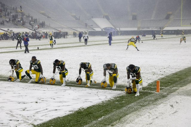 Some Green Bay Packers players pause at the goal line before an NFL football game against the Tennessee Titans Sunday, December 27, 2020, in Green Bay, Wis. (Photo by Mike Roemer/AP Photo)