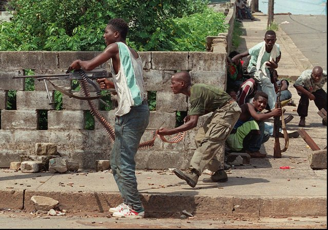 Liberian factional fighters loyal to Charles Taylor's National Patriotic Front of Liberia (NPFL) fire a high caliber machine gun at rival fighters loyal to Roosevelt Johnson, near the Barclay Training Center compound in downtown Monrovia Saturday, May 4, 1996. Despite the evacuation of Johnson from Monrovia to Accra, Ghana, Friday, heavy fighting continued in the Liberian capital city. (Photo by David Guttenfelder/AP Photo)