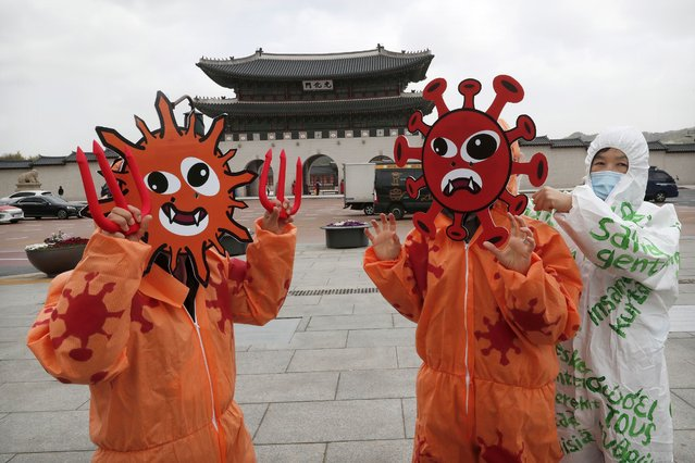 Members of the Environmental Health Citizens' Association of Korea wearing masks representing the viruses perform during an event to celebrate the 50th anniversary of Earth Day at Gwanghwamun Square in Seoul, South Korea, Wednesday, April 22, 2020. For most people, the new coronavirus causes only mild or moderate symptoms, such as fever and cough. For some, especially older adults and people with existing health problems, it can cause more severe illness, including pneumonia. (Photo by Ahn Young-joon/AP Photo)