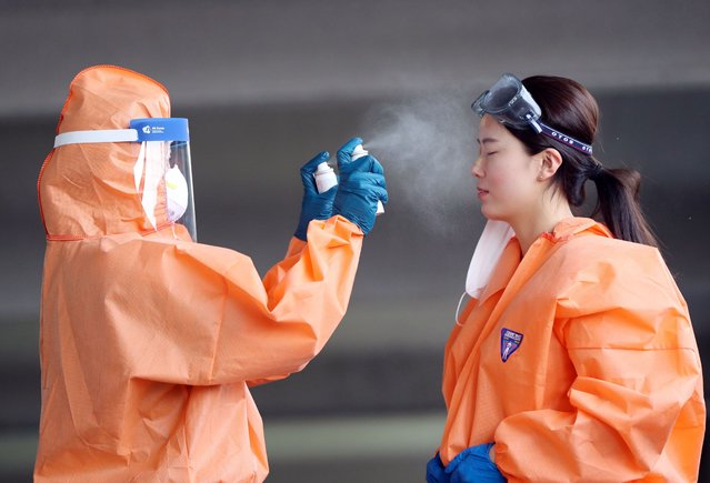 A medical worker in protective gear sprays mist on her colleague during a hot day at an outdoor clinic for coronavirus tests at a public health facility in the southwestern city of Gwangju, South Korea, 05 June 2020. (Photo by Yonhap/EPA/EFE)