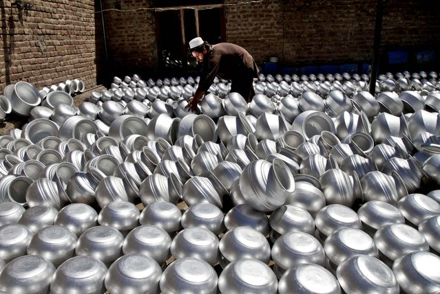 A laborer arranges pots at an aluminum factory in Jalalabad, Afghanistan, on June 5, 2013. Men working at the factory earn an average of $ 7.28 per day. (Photo by Rahmat Gul/Associated Press)