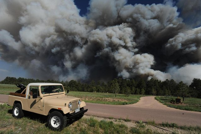 Bill Moreau watches as the Black Forest fire burns near his house near Black Forest Road Tuesday afternoon, June 11, 2013, near Colorado Springs, Colo. The Black Forest Fire was one of at least three significant wildfires burning in Colorado amid gusty winds and record-breaking hot, dry weather. (Photo by Christian Murdock/AP Photo/The Colorado Springs Gazette)