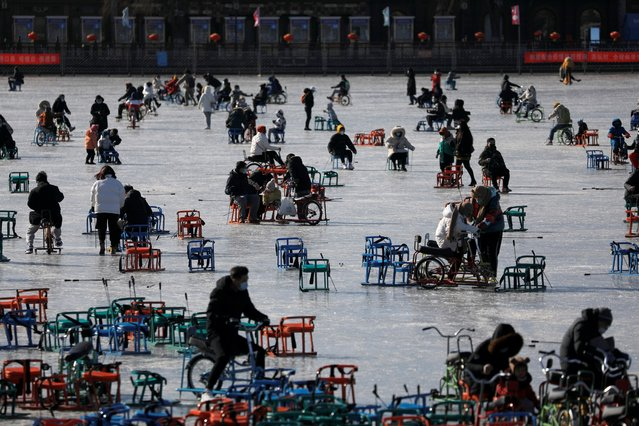People wearing face masks following the coronavirus disease (COVID-19) outbreak skate on a frozen lake which has been turned to an ice rink, in Beijing, China, January 16, 2021. (Photo by Tingshu Wang/Reuters)