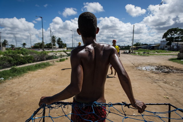 A young man leans on a handmade goal as he plays football in a shantytown of Olinda, about 18 km from Recife in northeastern Brazil, on June 18, 2013 as the FIFA Confederations Cup Brazil 2013 football tournament is being held in the country. The historic centre of Olinda is listed as an UNESCO World Heritage Site. (Photo by Yasuyoshi Chiba/AFP Photo)