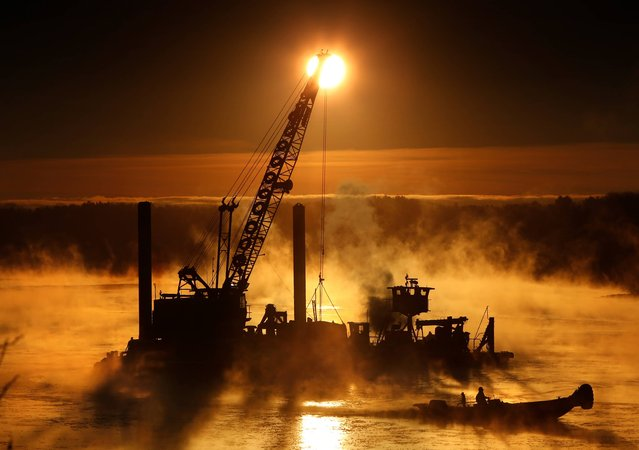 Arctic sea smoke rises on the Royal River in Yarmouth, Maine, as a worker uses a push boat to break ice forming around a dredging operation, Wednesday morning, January 14, 2015. The temperature at sunrise was minus 8 degrees. Sea smoke occurs when extremely cold air passes over warmer water. (Photo by Robert F. Bukaty/AP Photo)