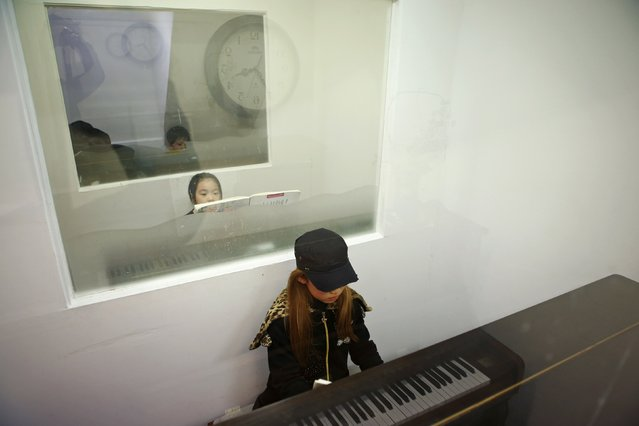 Kim Si-yoon plays the piano during a lesson in Seoul November 20, 2014. Nine-year-old Kim has no time to throw tantrums. (Photo by Kim Hong-Ji/Reuters)
