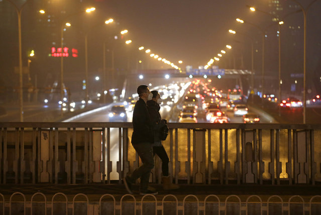 "People wearing protective masks walk through an overpass during the evening rush hour amid the heavy smog after Beijing issued its first red alert for air pollution in Beijing, China December 7, 2015. China's capital on Monday issued its first ever ""red alert"" for pollution, as the city government warned that Beijing would be shrouded in heavy smog from Tuesday until Thursday. (Photo by Jason Lee/Reuters)"