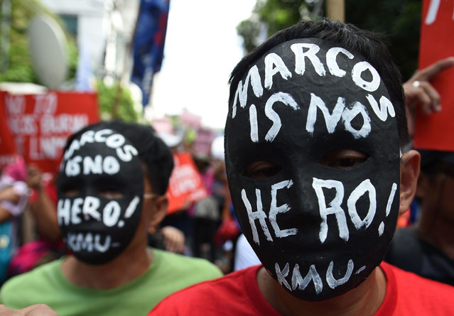 "Activists wear masks with anti- Marcos slogans during a rally in front of the Supreme court in Manila on November 8, 2016, as they await the high court' s decision on whether to allow the burial of the late Philippine dictator Ferdinand Marcos at the ""Cemetery of Heroes"" Marcos can be buried at the national heroes' cemetery, the Supreme Court ruled on November 8 in a hugely controversial verdict that critics warned would whitewash his crimes and divide the nation. (Photo by Ted Aljibe/AFP Photo)"