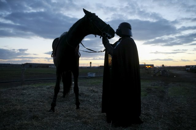 Darth Mykolaiovych Vader, who is dressed as the Star Wars character Darth Vader, poses for a picture as he caresses his horse at a stabling outside of Odessa, Ukraine, December 2, 2015. (Photo by Valentyn Ogirenko/Reuters)