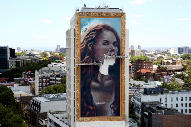 Finishing touches are applied to the portait as seen from the Zenith building on November 14, 2020 in Sydney, Australia. A team of 11 artists have been working over two weeks to hand paint an 18-story portrait of Nicole Kidman on a building overlooking Sydney's Kings Cross. The 18.4 x 36.8-metre painting is the largest of its kind in the Southern Hemisphere. (Photo by Don Arnold/WireImage)