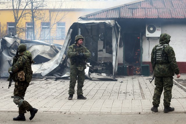 Ukrainian servicemen stand guard near a destroyed shop after shelling in the southern Ukrainian port city of Mariupol on 24, 2015. At least 27 people died Saturday in a rocket attack on Ukraine's strategic government-held port of Mariupol after Russian-backed rebels rejected peace talks, the mayor's office said. (Photo by AFP Photo/Stringer)