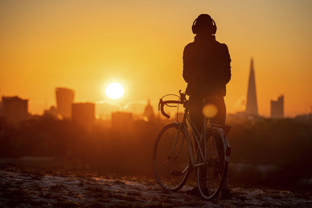 A cyclist watches the sun rise, in Primrose Hill, London, Monday, January 25, 2021. (Photo by Aaron Chown/PA Wire via AP Photo)