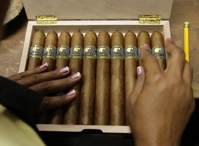 """A woman fills a box of high end """"Behike 56"""" cigars at the Cohiba factory """"El Laguito"""" in Havana September 10, 2012. (Photo by Desmond Boylan/Reuters)"""