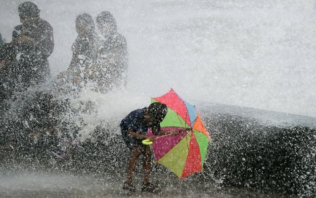 An Indian boy holds an umbrella as waves break over a seawall while monsoon rain falls, on July 25, 2013. The monsoon season, which runs from June to September, accounts for about 80% of India's annual rainfall, vital for a farm economy which lacks adequate irrigation facilities. (Photo by Punit Paranjpe/AFP Photo)