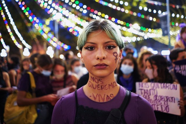 """Participant with words that read """"We want to be alive"""" written on her neck, looks on as they mark International Women's Day in downtown Montevideo, Uruguay on March 8, 2021. (Photo by Mariana Greif/Reuters)"""