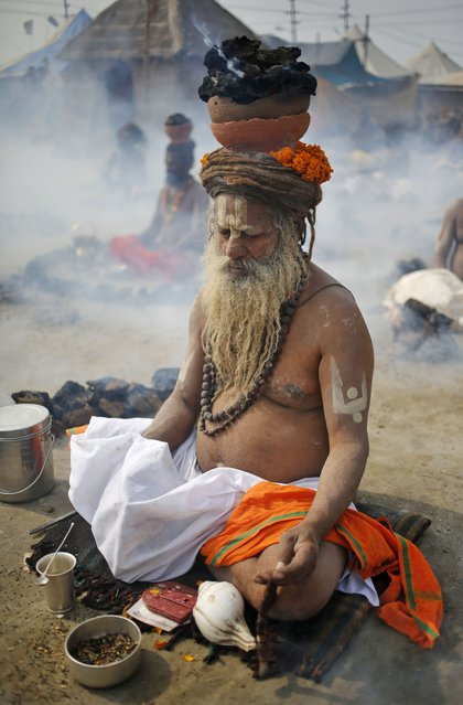 "A Sadhu, or Hindu holy man performs a ritual by burning dried cow dung cakes in earthen pots overhead in his quest for salvation at Sangam, confluence of rivers Ganges, Yamuna, and mythical Saraswati, on the auspicious occasion of ""Basant Panchami"" at the annual traditional fair of Magh Mela in Allahabad, India, Saturday, January 24, 2015. (Photo by Rajesh Kumar Singh/AP Photo)"